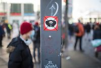 """Anlaesslich des ertsne Jahrestag der Coronamassnahmen der Bundesregierung protestierten etwas ueber 200 Menschen auf dem Berliner Alexanderplatz gegen die Politik der Bundesregierung. Sie forderten ein Ende der Maskenregelungen und Einschraenkungen in oeffentlichen Leben. Die Demonstranten riefen """"Liebe, Freiheit, Keine Diktatur"""" und """"Wahrheit macht Frei"""".<br /> Der Veranstalter, der Youtube-Schlagerstar Bjoern Winter alias Bjoern Banane, hatte 1000 Menschen zu der Kundgebung erwartet.<br /> Im Bild: Ein Aufkleber im Stile der Hakenkreuzfahne der Nationalsozialisten, rote Fahne mit weisem Kreis und schwarzem Symbol, auf dem die sog. Merkel-Raute durchgestrichen ist. Dieser Aufkleber wird von sog. Antideutschen, wie auch on Rechtsextremen verklebt.<br /> 13.3.2021, Berlin<br /> Copyright: Christian-Ditsch.de"""