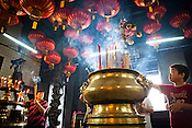 Devout Chinese light up incense sticks while offering prayers at the Goddess of Mercy temple in capital Georgetown of Penang, The Goddess of Mercy Temple or Kuan Yin Ting is the oldest Chinese temple in Penang, built in 1880s by early immigrants from China. Malaysia. Photo: Sanjit Das/Panos