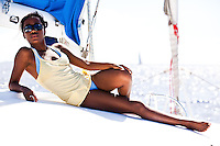 Young black woman relaxing on deck of sailboat in bikini and tank top