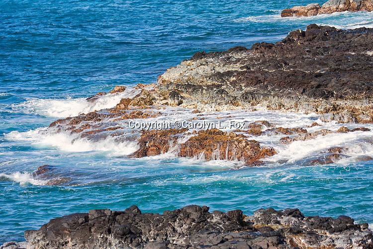 Waves splash violently against rocks in Hawaii.