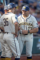 Michigan Wolverines head coach Erik Bakich (23) talk with assistant coaches Michael Brdar (36) and Nick Schnabel (23) before playing the Vanderbilt Commodores in Game 1 of the NCAA College World Series Finals on June 24, 2019 at TD Ameritrade Park in Omaha, Nebraska. Michigan defeated Vanderbilt 7-4. (Andrew Woolley/Four Seam Images)