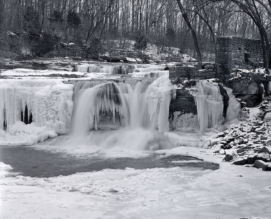 """"""" Cataract Ice""""<br /> Cataract Falls, Owen County<br /> 2009<br /> <br /> Near the village of Cataract is one of Indiana's hidden beauties.  Cataract Falls are   located in Lieber State Recreational Area.  Mill Creek meanders slowly through Owen County before making its descent over the cascades and two falls.  The waters flow over the preglacial limestone bedrock creating curved ridges.  The cascade tumbles over the rock steps resembling a grand staircase.  The bubbling creek forms a veil of white as it falls onto the next level of rocks.  The falls provide a totally different view during the winter.  At this time of year, great ice formations with their delicate abstract textures form creating a scene that is perfect for a black and white image.<br /> <br /> 4 x 5 Large Format Film"""