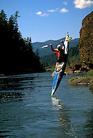 A kayaker in mid-air during rock jumping. Rogue River, Oregon.