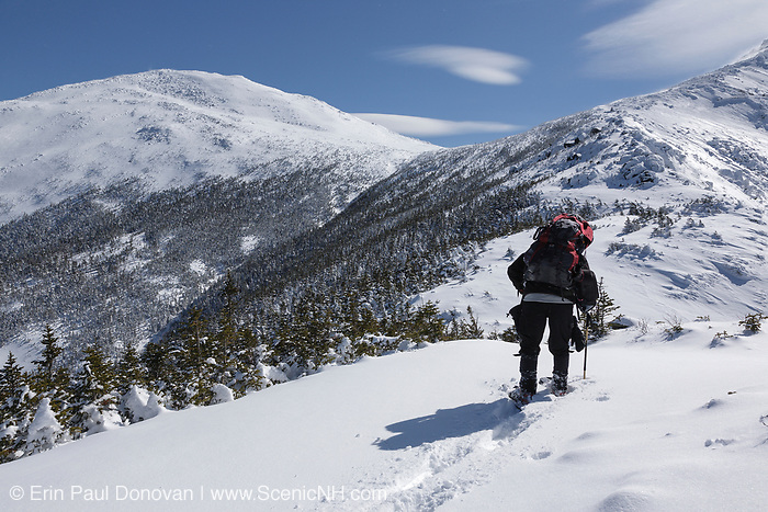 A winter hiker ascending the Air Line Trail in the White Mountains, New Hampshire during the winter months.