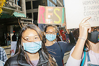 """Protestors march along Tremont Street as they make their way to Boston City Hall during the 2020 Women's March protest in opposition to the re-election of US president Donald Trump in Boston, Massachusetts, on Sat., Oct. 17, 2020.<br /> The signs here read """"Resist"""" and """"Resist: sexism, racism, xenophobia, homophotobia, ignorance, corruption, and hate."""""""