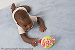 5 month old baby boy on stomach full length interested in toy reaching for toy African American horizontal