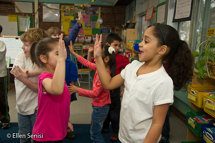 MR / Schenectady, New York. Paige Elementary School (urban public elementary school). First grade classroom. Students move together with music in classroom creative movement activity. Girls in front: 7. MR: Dei1, Liv3. ID: AL-g1g. © Ellen B. Senisi.