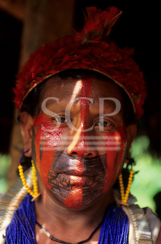 A-Ukre, Brazil. Kakuyi, a Kayapo Indian warrior, with red urucum and black genipapo face paint and red feather headdress, bead necklaces and earrings. Para State.