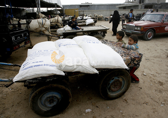 Palestinians receive their monthly food aid at a UN distribution center in the Rafah refugee camp, southern Gaza Strip on February 26, 2012.  Photo by Abed Rahim Khatib