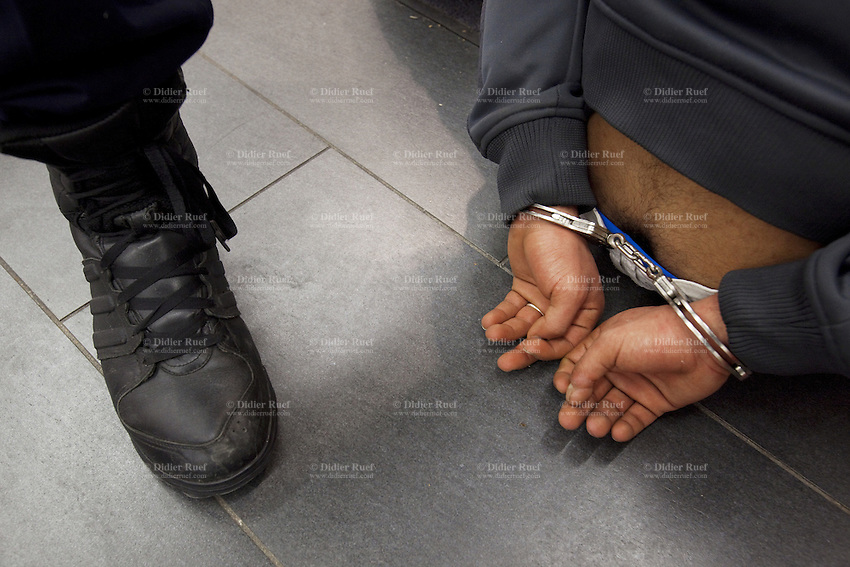 Switzerland. Geneva. Railway station. Aperto shop. A police officer and a handcuffed man. The inmate is an arab man from the Maghreb area. He is arrested by the policeman for stealing articles in the shop. 24.03.12 © 2012 Didier Ruef..