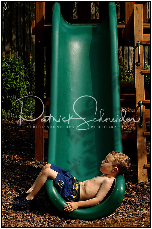 A young boy relaxes on a green slide after playing in a backyard sprinkler. Photo is model released, can be used for multiple purposes.
