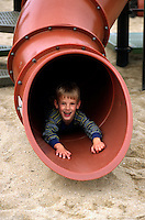 A 7 year old BOY plays on a slide (MR)