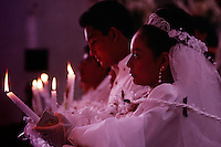 Maria del Carmen Matos and Gerardo Ulloa kneel in prayer holding candles during their wedding ceremony at the cathedral. The bride and groom were one of three getting married on the weekend. Their party was complete with traditional food and dancing in the street. After the church wedding, the couple walks through the streets of town following musicians.