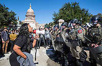 AUSTIN, TEXAS - NOV. 20, 2016 - A demonstrator with a bullhorn addresses the riot police at the Texas State Capitol during a White Lives Matter and Black Lives Matter demonstration.<br /> <br /> Police in riot gear take guard as White Lives Matter protesters were confronted by counter-demonstrators supporting Black Lives Matter at the Texas State Capitol near where Gov. Greg Abbott had earlier dedicated a monument recognizing the contribution of African-Americans to the state.<br /> <br /> Use of this image in advertising or for promotional purposes is prohibited.<br /> <br /> Editorial Credit: Photo by Dan Herron / Herron Stock