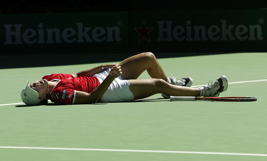 A distressed Justine Henin-Hardenne of Belguim lies on centre court suffering from a cramp during the final stages of her marathon fourth round match against Lindsay Davenport at the 2003 Australian Open. -pic by Trevor Collens