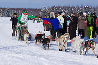 Sunday, March 4, 2012  Kelly Maxiner getting high fives from fans on Long Lake at the restart of Iditarod 2012 in Willow, Alaska.