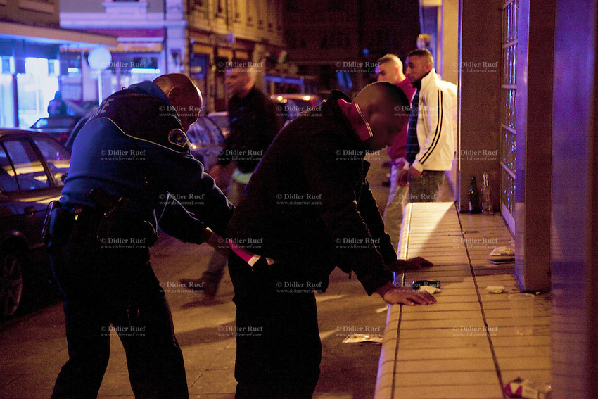 Switzerland. Geneva. A police officer control the identity of a man in the street and look for illegal substances (drugs). The man comes from the neighboring french area and wants to party in the Paquis neighborhood, known for its nightlife and Red-light district. He will be left free after the control. The policeman is wearing a ballistic vest, bulletproof vest or bullet-resistant vest which is an item of personal armor that helps absorb the impact from knives, firearm-fired projectiles and shrapnel from explosions, and is worn on the torso. Soft vests are made from many layers of woven or laminated fibers and can be capable of protecting the wearer from small-caliber handgun and shotgun projectiles. 01.04.12 © 2012 Didier Ruef..
