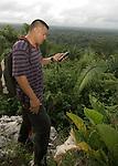 Ranger checks GPS on mountain overlooking Belize rainforest - Sarstoon-Temash National Park.