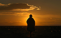 """Una mujer de la etnia aymara camina durante el atardecer a través del desierto que rodea la ciudad de Uyuni en la región sur de Bolivia.+ indio,   sol,  paisaje *An aymara indian woman walks at sunset  through the desert sourrounding  Uyuni city , in Southern Bolivia +landscape *Une femme de l'ethnie Aymara dans le désert aux abords de la ville, dans le sud de la Bolivie, au coucher du soleil. +indiens, indigènes, paysage For  the first time in its history,  in January 2014 the Dakar Rally will  be cross part of Bolivia, one of the wildest South American nations.  """"The organizers of the Dakar, attracted by the discovery of new spaces, were conquered by Bolivian landscapes that can be classified among the most striking of the continent,"""" says the official site of the international race.<br /> The most impressive is the section that runs through the Salar of Uyuni,  considered the world's largest salt flat and a place of surreal beauty, almost otherworldly.<br /> The competition is scheduled for  in January 2014. Our photographer and  friend Patricio Crooker  show us  the unique beauty of the places the rally will hit."""