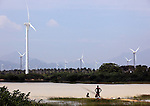 23 November 2011:  Locals wash among wind turbines at a vast wind farm in the shadow of the Koodankulam Nuclear Power Plant  currently under construction in Tirunelveli district of the southern Indian state of Tamil Nadu.  The People's Movement Against Nuclear Energy has organised rally's and hunger strikes at the site in an effort to close the facility but have seemingly failed in their on going campaign.   Picture by Graham Crouch