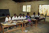 The Gambia; Africa. A rural schoolroom with pupils at desks full of exercise books.