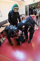 Nach einer Woche Aufenthalt im Haus des Deutschen Gewerkschaftsbunds in Berlin liessen die Verantwortlichen des DGB etwa 25 Fluechtlinge durch die Polizei raeumen. Dabei gab es mehrere Verletzte, zwei davon nach Aussagen von Augenzeugen schwer. Mehrere Fluechtlinge wurden nach der gewaltsamen Raumung ins Krankenhaus gebracht. Mehrere Personen hatten sich zum Teil aneinander gekettet, um so die Raeumung zu verhindern.<br /> Die Fluechtlinge hatten vor einer Woche im DGB-Haus um Unterstuetzung fuer ihr Anliegen nach Asyl und Bleiberecht gesucht. Die Gewerkschaftsverantwortlichen waren jedoch nicht bereit ihnen mehr als ein paar Tage Obdach zu gewaehren und die Politik zu bitten das Problem zu loesen.<br /> Im Bild: Polizei im Gewerkschaftshaus bei der Raeumung. Der Fluechtling wurde mit dem Rest der Kette stranguliert und ist ohnmaechtig zusammenbrechen. Zuvor ist im bei der Festnahme die Nase blutig geschlagen worden.<br /> 2.10.2014, Berlin<br /> Copyright: Christian-Ditsch.de<br /> [Inhaltsveraendernde Manipulation des Fotos nur nach ausdruecklicher Genehmigung des Fotografen. Vereinbarungen ueber Abtretung von Persoenlichkeitsrechten/Model Release der abgebildeten Person/Personen liegen nicht vor. NO MODEL RELEASE! Don't publish without copyright Christian-Ditsch.de, Veroeffentlichung nur mit Fotografennennung, sowie gegen Honorar, MwSt. und Beleg. Konto: I N G - D i B a, IBAN DE58500105175400192269, BIC INGDDEFFXXX, Kontakt: post@christian-ditsch.de<br /> Urhebervermerk wird gemaess Paragraph 13 UHG verlangt.]
