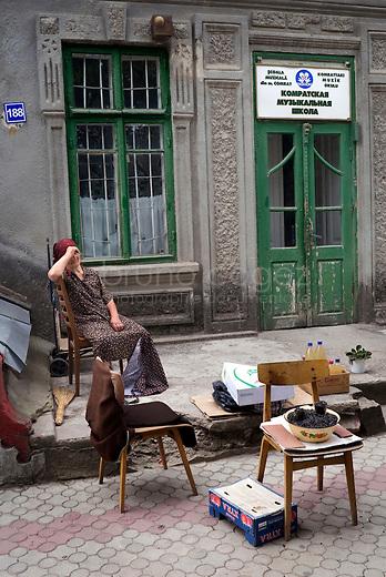 REPUBLIC OF MOLDOVA, Gagauzia, Comrat, 2009/06/26..A saleswoman of sunflower seeds in the center of Comrat, the capital of Gagauzia, in front of the music school. Pensioners often live with less than 50 EUR per month. Small businesses have developed well throughout Moldova..© Bruno Cogez..REPUBLIQUE MOLDAVE, Gagaouzie, Comrat, 26/06/2009..Une vendeuse de graines de tournesol dans le centre de Comrat, la capitale de la Gagaouzie, devant l'école de musique. Les retraités vivent souvent avec moins de 50EUR par mois. Les petits métiers se sont ainsi développés dans toute la Moldavie..© Bruno Cogez