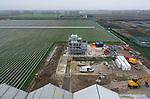 Foto: VidiPhoto<br /> <br /> BEMMEL – In kassengebied NextGarden (voorheen Bergerden) bij Bemmel wordt woensdag hard gewerkt aan een gloednieuwe biomassacentrale. Hoewel de bouw enige vertraging heeft opgelopen, verwacht opdrachtgever Lingezegen Energy BV -een initiatief van veertien tuinders- in april te kunnen starten met het leveren van energie. De installatie wordt gestookt op snoei- en afvalhout van de meubelindustrie en moet de kassen verwarmen. NextGarden wil als eerste kassengebied van Nederland in 2025 energieneutraal zijn. De biomassacentrale levert een vermogen van 14.9 MWh. Een poging van milieuactiviteit Johan Vollenbroek om de bouw stil te laten leggen mislukte. Volgens hem zouden de vergunningen niet in orde zijn.