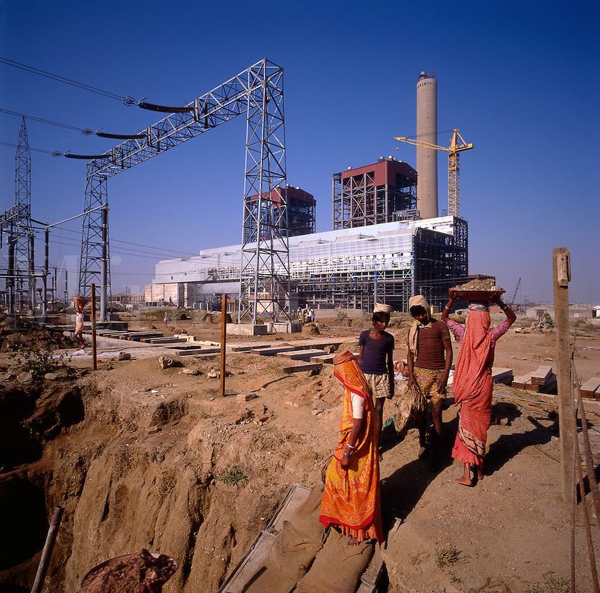 India. Rihand.  Local women and young men manually removing rubble from large excavations on power station site..