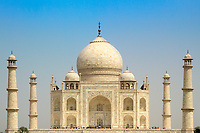 Iconic Taj Mahal ivory-white marble mausoleum symmetry under a blue sky, on the bank of the Yamuna river in Agra, Uttar Pradesh, India