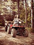 Young farm woman gardener riding an ATV with a trailer along countryside road. Muskoka, Ontario, Canada.