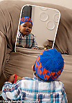 17 month old toddler boy looking at self in mirror recognizing self wearing hat (Muslim practice)