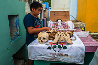 """A Mayan boy cleans dried-up bones of a deceased family member during the bone cleansing ritual at the cemetery in Pomuch, Mexico, 28 October 2019. Every year on the Day of the Dead, people of Pomuch, a small Mayan community in the south of Mexico, visit the cemetery to take part in a pre-Hispanic tradition of cleaning of bones of their departed relatives (""""Limpia de huesos""""). People who die in Pomuch are firstly buried for three years in an above-ground tomb then the dried-up bodies are taken out, bones are separated, wrapped in a decorated cloth, put into a wooden crate, and placed on display among flowers for veneration."""