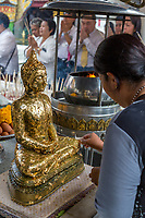 Bangkok, Thailand.  Worshipers Placing Gold Leaf on Buddha Statue, Royal Grand Palace Compound.