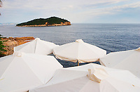 White sun shade umbrellas at a cafe on the city wall overlooking the sea and the Lokrum island Dubrovnik, old city. Dalmatian Coast, Croatia, Europe.