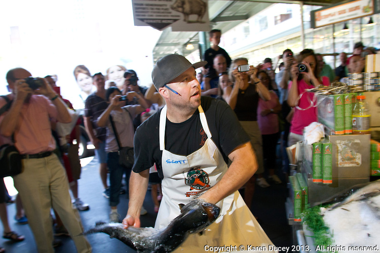 Scott Smith tosses a wild-caught King salmon from Alaska to the counter of the Pike Place Fish Market in Seattle, Wash., on July 1, 2013. (photo © KarenDucey.com)