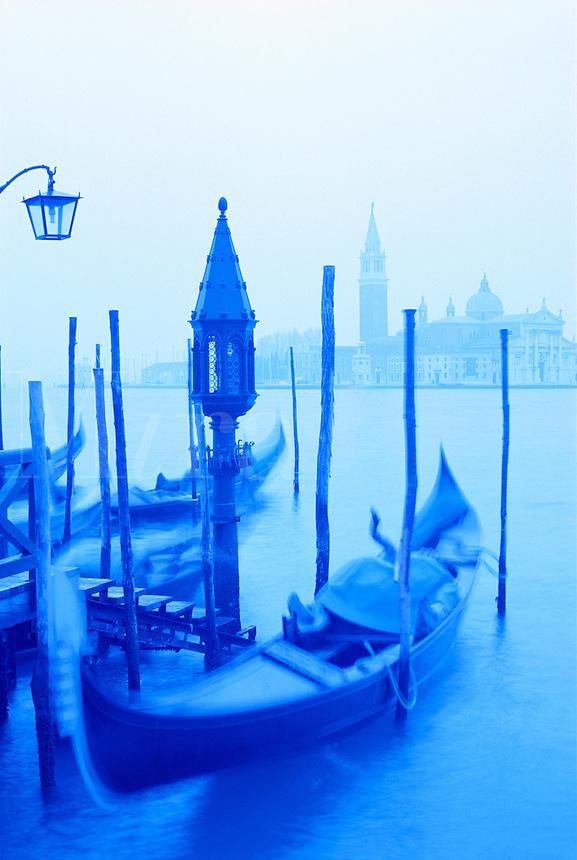 Italy, Venice. Gondola and San Giorgio  Maggiore in blue tones. Gondolas moored at Molo San Marco at dusk.
