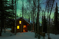 Man steps out of a log cabin in a boreal forest in Fairbanks, Alaska with green northern lights overhead