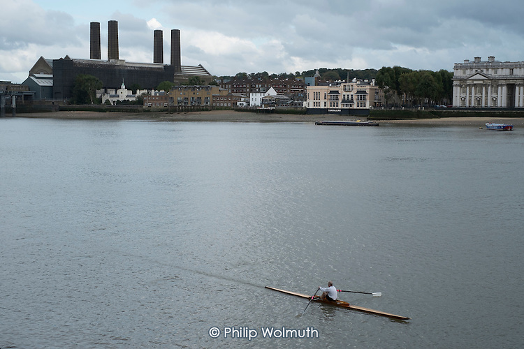 Canoeists on the river Thames London row past Greenwich Power Station