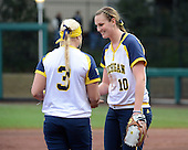 Michigan Wolverines pitcher Sara Driesenga (10) hands the ball to relief pitcher Megan Betsa (3) during the season opener against the Florida Gators on February 8, 2014 at the USF Softball Stadium in Tampa, Florida.  Florida defeated Michigan 9-4 in extra innings.  (Copyright Mike Janes Photography)
