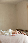 Young woman wearing white reclining in bed