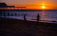 Aberystwyth, UK 23rd February 2016 local people watch the sun setting by Aberystwyth pier in west Wales.