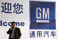 A man chats on his mobile phone while standing in front of an advertisement for GM in Shanghai, China. GM is in partnership with the Shanghai Automotive Industry Corp (SAIC) to supply the Chinese market..