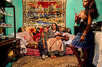 Petrace Marieana sits with her grandchildren, Bobi and Miralela, while their neighbour, Florina, arranges her hair. Buzescu is known for it's ultra-wealthy Roma and their bizarre mansions that line the main street. The Roma of Buzescu are part of the Kalderash clan and are known for being coppersmiths and dealing with metal scraps. After the fall of the communist regime in the late 80's, they stripped old factories of their metals and some made a small fortune re-selling them. They are also known for making cazane, copper stills that produce alcohol such as palinka, a plum brandy.
