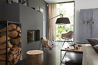 An Eames armchair is matched with a distressed rustic armoire beside the minimal fireplace in the living room