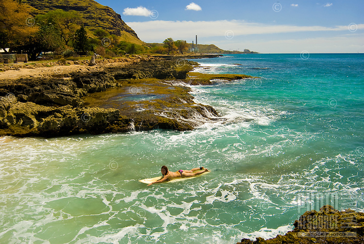 Young woman returning from surfing at Makaha