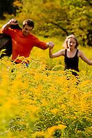 Couple running through field of goldenrod