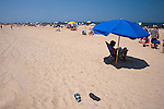 A summer beach goer has abandoned his sandals in favor of the shade under his umbrella.  Rehoboth Beach, Delaware, USA.