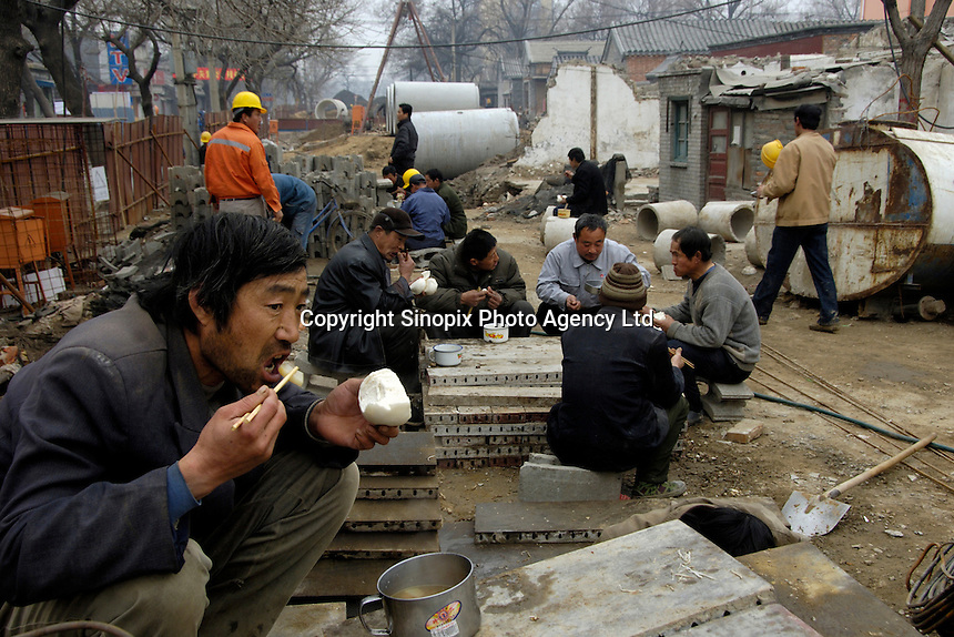 Chinese migrant workers eat lunch near a construction site in Beijing. China will face huge job pressures this year with 12 million urban dwellers expected to be out of work and an army of rural workers crowding into cities with the bleak forecast based on estimates that 24 million people -- or more than the entire population of Australia -- will enter the job market in 2007..