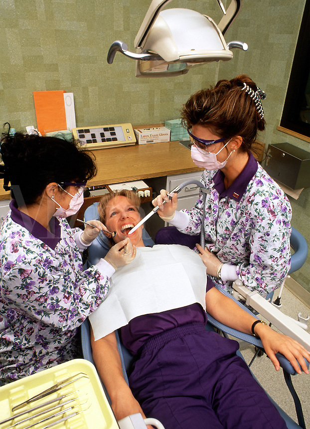 A female patient in a dentist's office receives a teeth cleaning from dental hygenists.